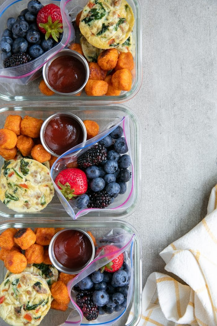 Three prepared breakfast meal prep trays with egg cups recipe, sweet potato tots, and fresh fruit