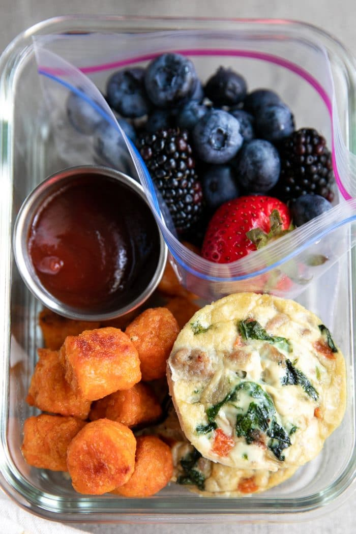 Easy breakfast meal prep with sausage and egg cups, sweet potato tots, fresh fruit, and a side of ketchup