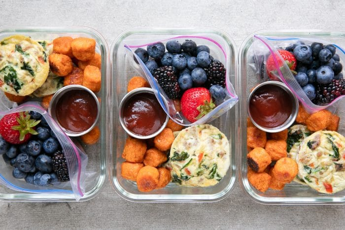 Overhead of packed and prepared breakfast meal prep trays with egg cups, fruit, and sweet potato tots.
