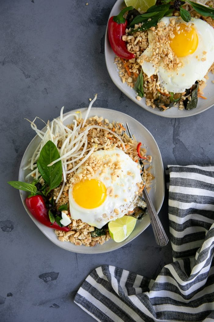 Thai fried rice topped with bean sprouts, peanuts, fried egg, and thai basil.