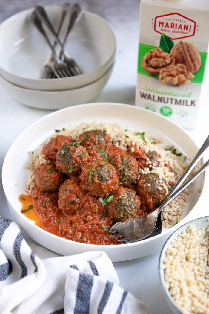 Cooked and plated lamb meatballs with couscous and a red saffron tomato sauce