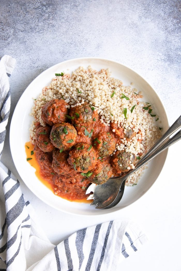 Platter with curried lamb meatballs in a saffron tomato sauce and couscous