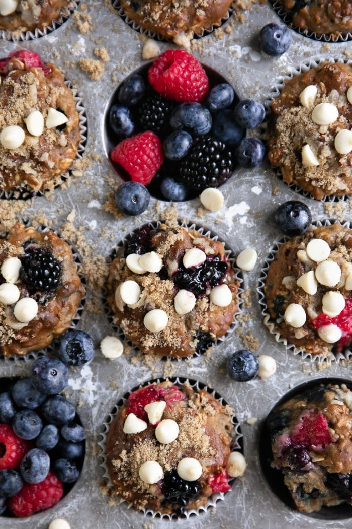 Close-up image of berry yogurt muffins still in muffin tin and topped with white chocolate chips