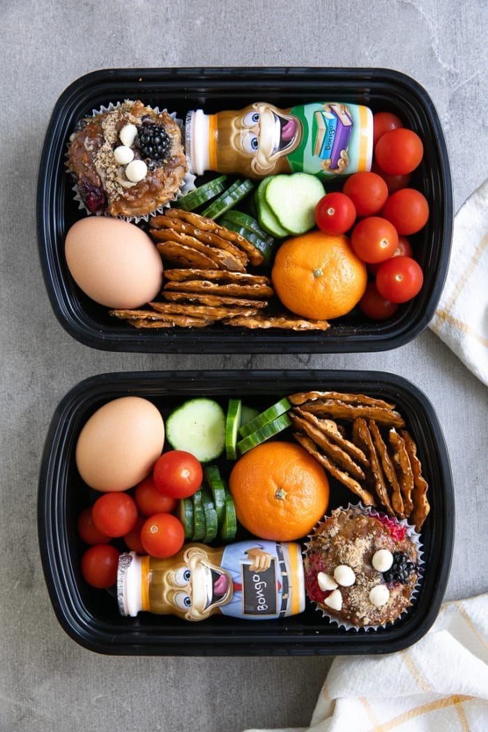 Two prepared back to school meal prep snack packs filled with fruit, veggies, muffins, and yogurt.