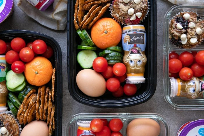 back-to-school meal prep trays with veggies, hard boiled egg, fruit, yogurt, muffins