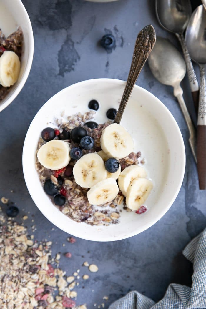 White Bowl filled with mixed berry instant oatmeal filled with milk and topped with banana.