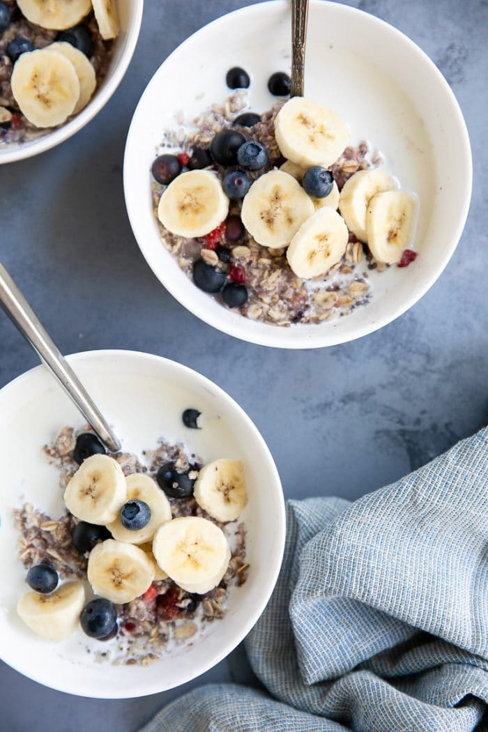 Instant berry oatmeal recipe topped with banana and drizzled with milk