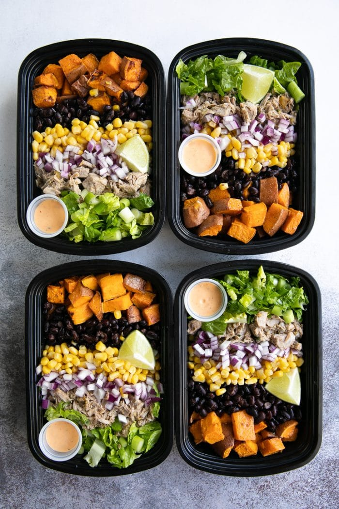 Four Meal Prep Bowls filled with roasted sweet potatoes, pork green chili, corn, beans, lettuce, and onion.