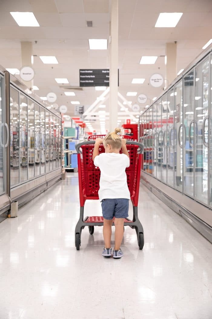 blonde boy pushing a red Target shopping cart