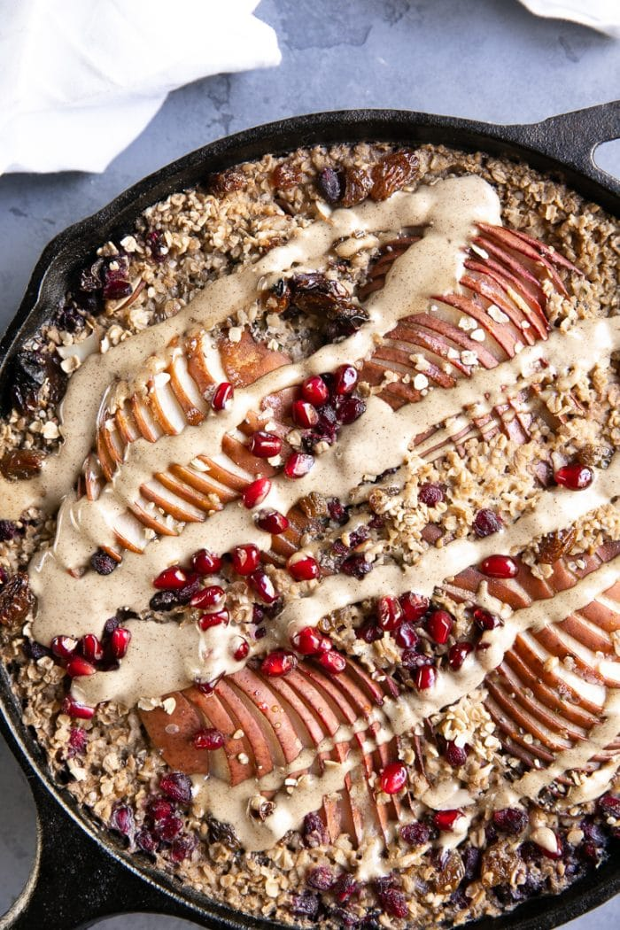 Large cast iron skillet filled with baked oats, pears, seeds, fruit, and nuts and drizzled with maple nut butter.