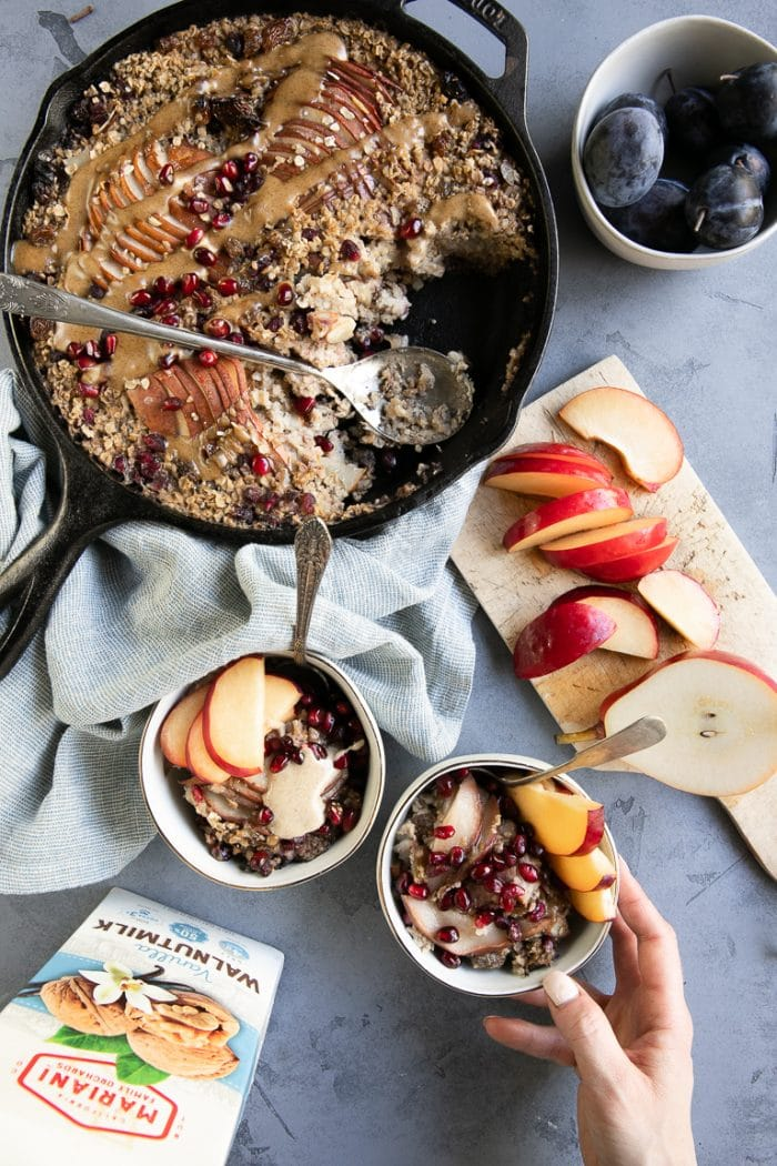 Table set with baked oatmeal skillet, sliced pears, and bowls filled with baked oatmeal