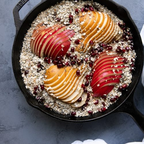 Cast iron skillet filled with rolled oats mixed with milk, pears, fruit, seeds, and nuts.