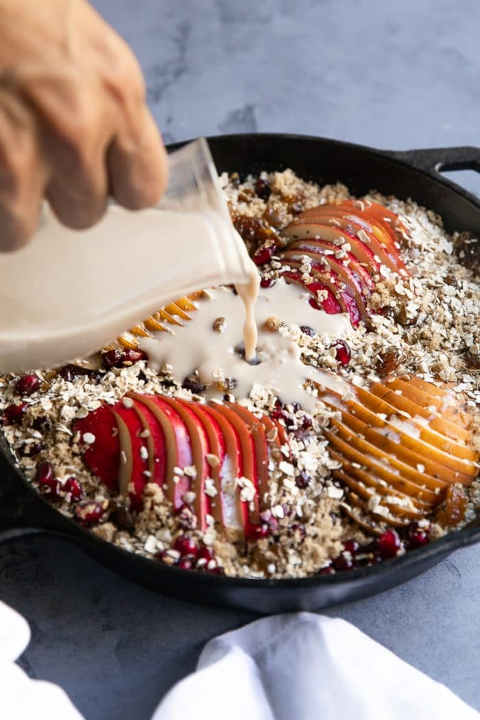 Milk being poured into a skillet filled with rolled oats mixed with milk, pears, fruit, seeds, and nuts.