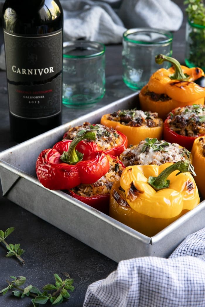 Food on a table, with Sausage and Stuffed peppers