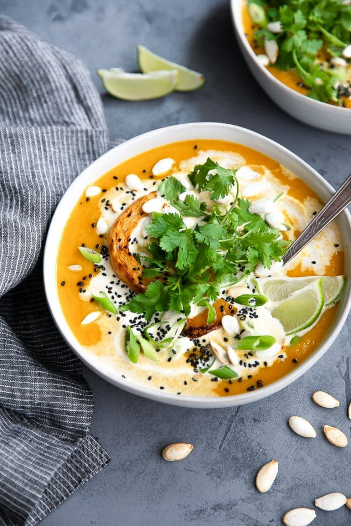 Bowl of vegan squash soup topped with roasted butternut squash, cilantro, and limes