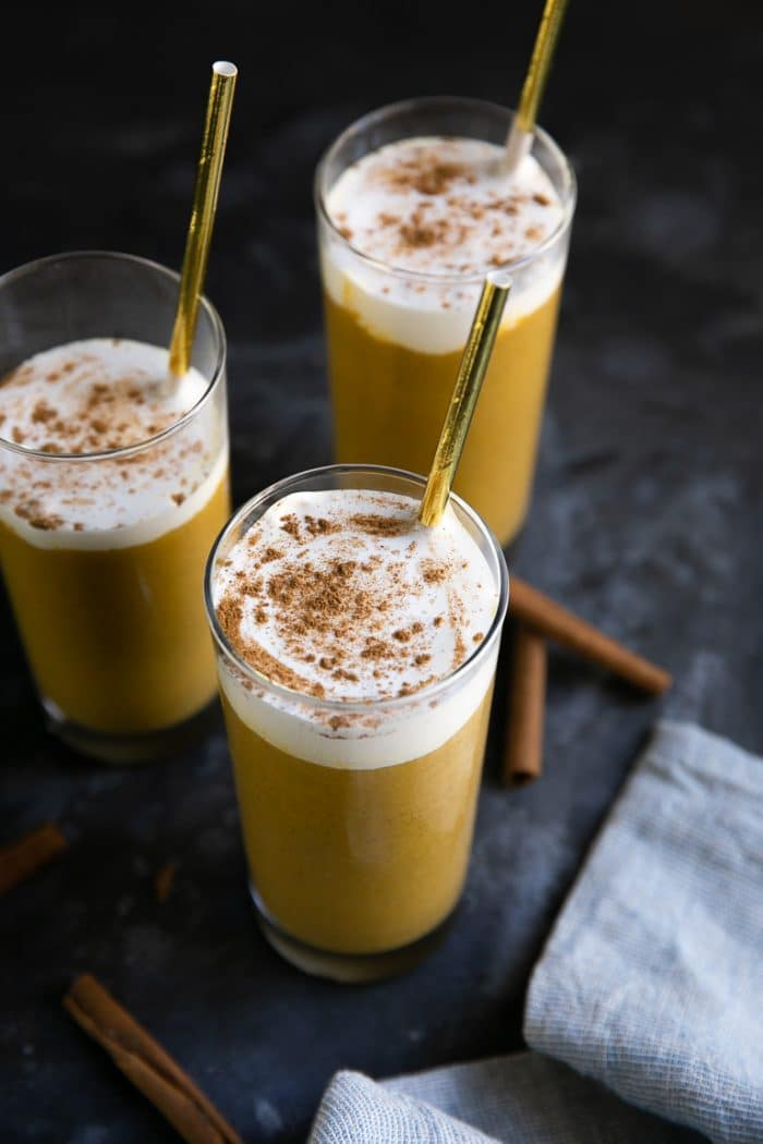 Three glasses filled with pumpkin smoothie and topped with whipped cream and sprinkled with cinnamon,