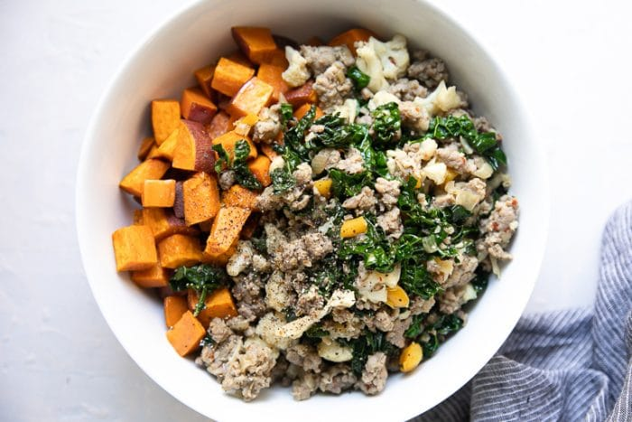 Bowl filled with cooked breakfast sausage, kale, and roasted sweet potatoes