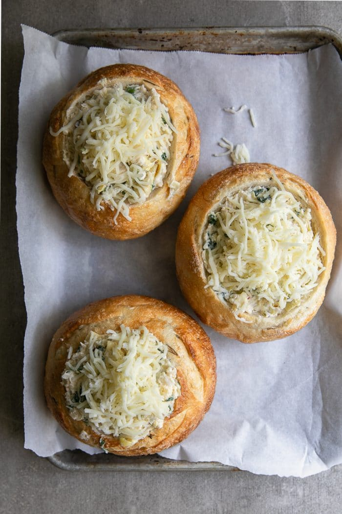 Three bread bowls hollowed out and stuffed with crab, spinach, and artichoke dip and topped with shredded mozzarella cheese.