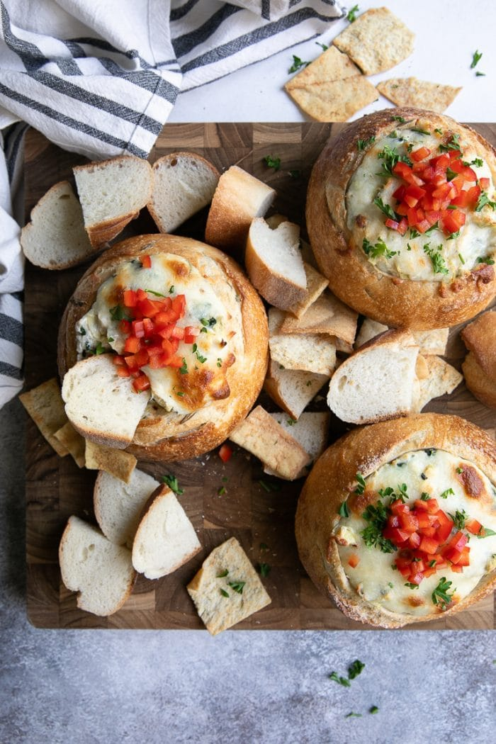 Baked and bubbly hot crab artichoke dip on a cutting board served with sliced baguette.