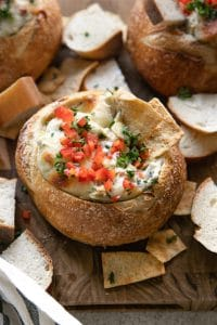 A bread bowl sitting on top of a wooden cutting board, filled with Hot Crab Artichoke Dip