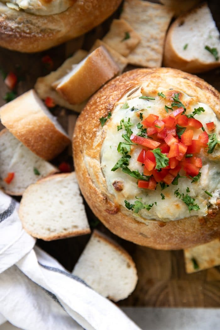 Overhead image on cheesy crab, spinach, and artichoke stuffed bread bowl baked and topped with chopped red bell pepper.