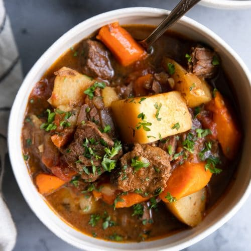 Two bowls filled with beef stew made in the Instant Pot and filled with juicy chunks of meat, carrots, and potatoes.