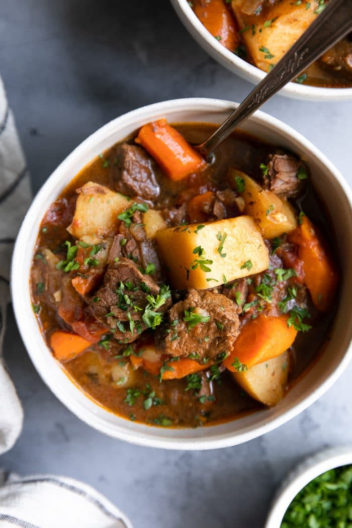 White bowl filled with beef stew made of carrots, beef, potatoes