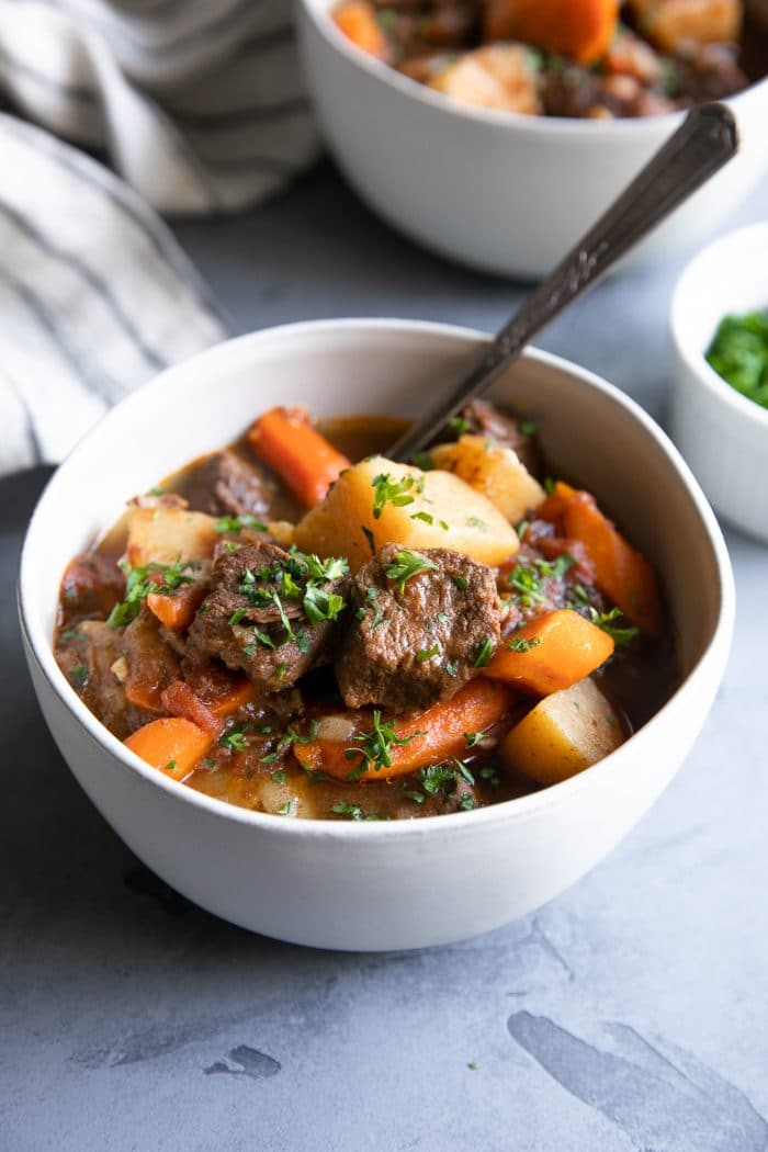 White bowls filled with juicy chunks of beef stew