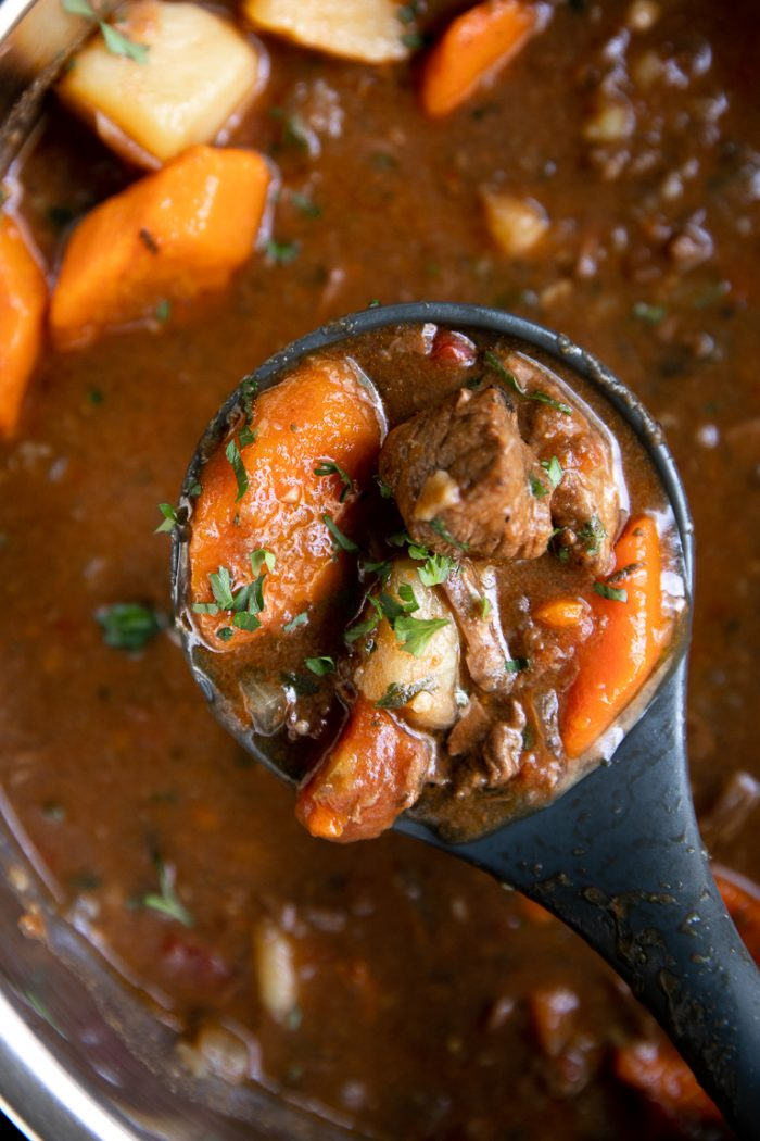 Ladle filled with comforting beef stew made with chunks of beef, carrots, and potato.