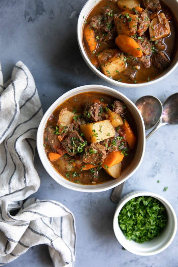 Overhead image of two bowls filled with beef stew made in the Instant Pot and garnished with fresh parsley.