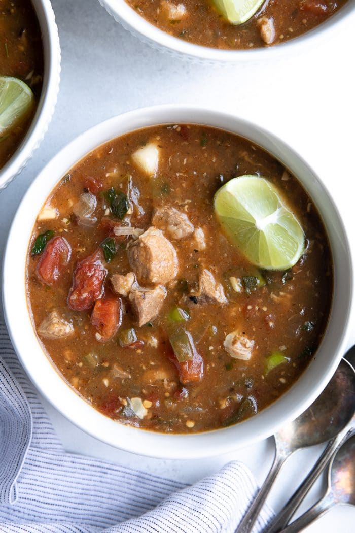 Overhead image of a white bowl filled with easy pork green chili stew  made with mild green chiles, tomatoes, chunks of tender pork shoulder, and garnished with a lime wedge.