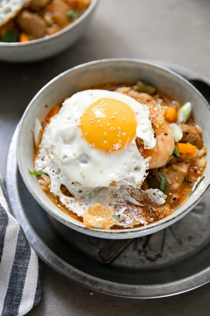 Bowl filled with jambalaya and topped with a fried egg.