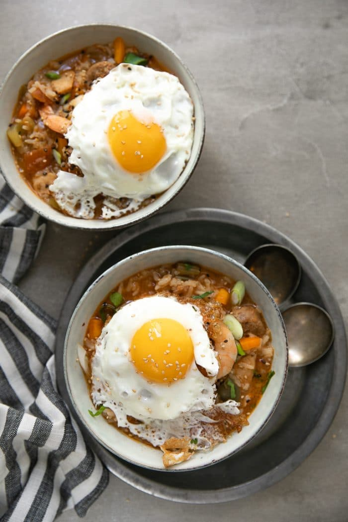 Two bowls filled with spicy jambalaya and each topped with a fried egg.