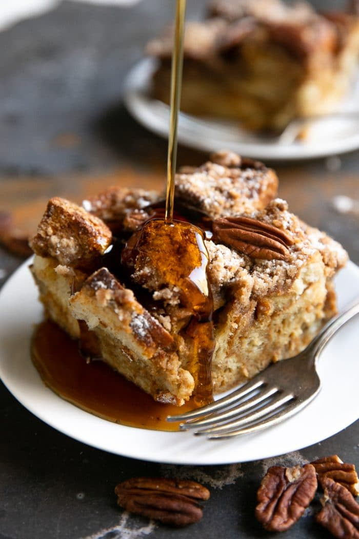 Pouring maple syrup onto a slice of French toast casserole