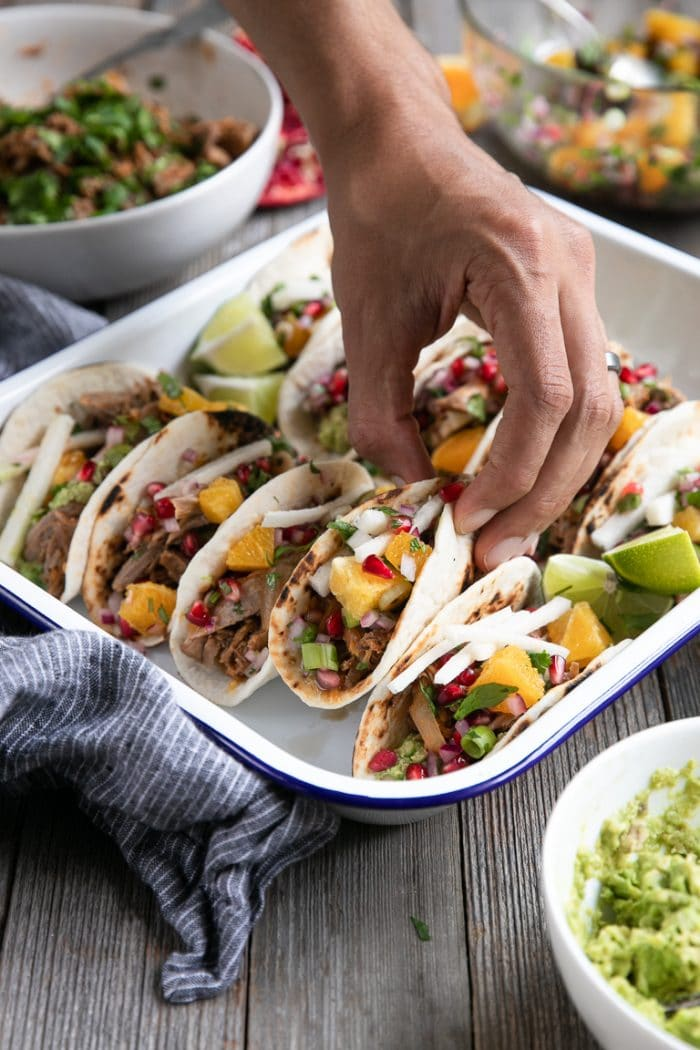 Hand taking a taco from a tray filled with prepared slow cooker harissa lamb tacos.
