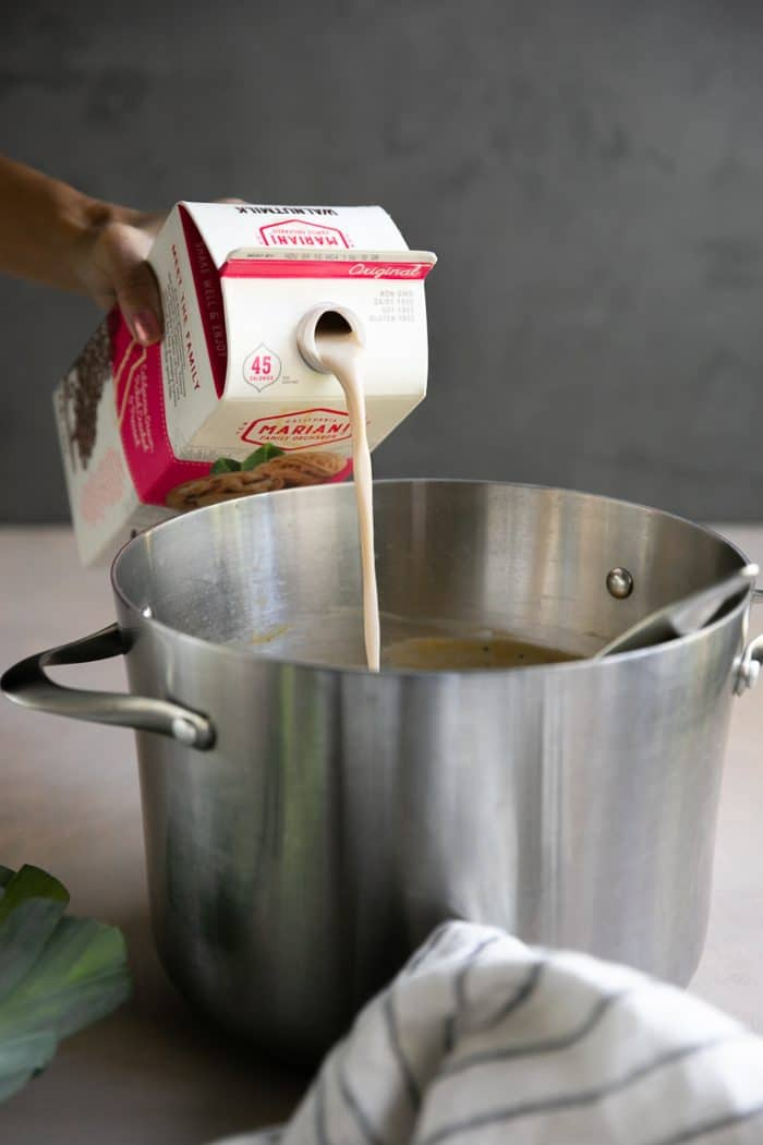 Pouring Mariani Walnutmilk into the pot of Leek and Potato Soup