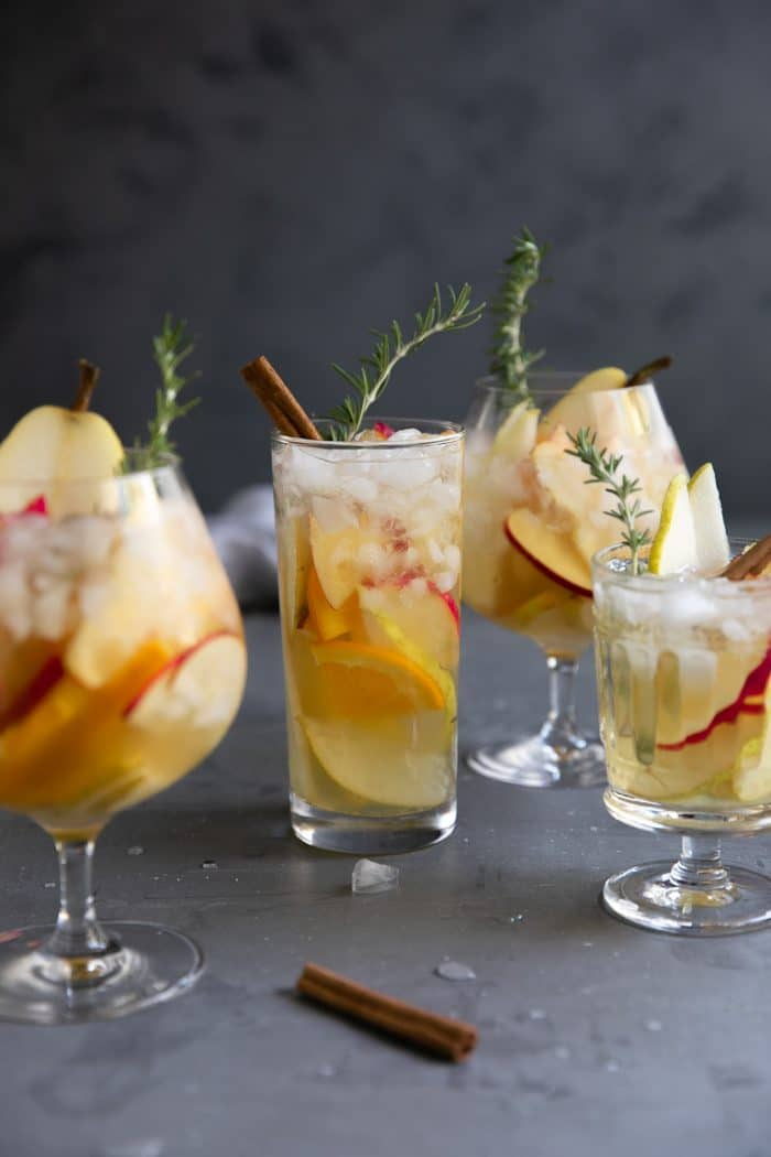 Four glasses filled with iced fall sangria and garnished with rosemary, pear, apple, and orange