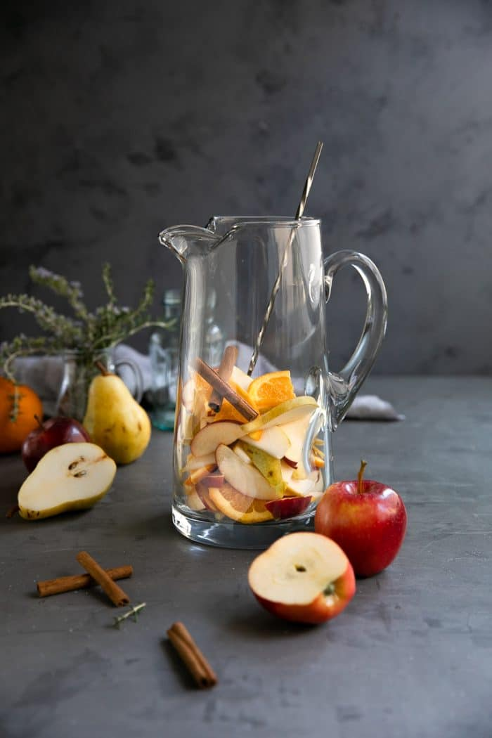Pitcher filled with sliced pear, apple, orange, and cinnamon sticks