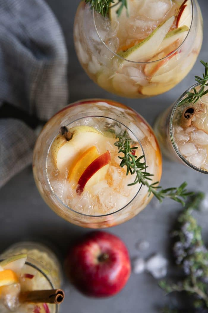 Overhead image of four glasses filled with iced pear and apple autumn sangria garnished with rosemary and pear