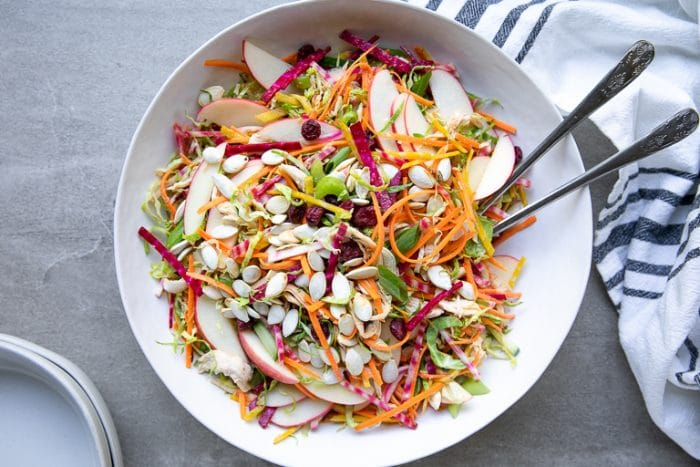 Large white salad bowl filled with Shredded Brussels Sprout Salad with Chicken and Beets