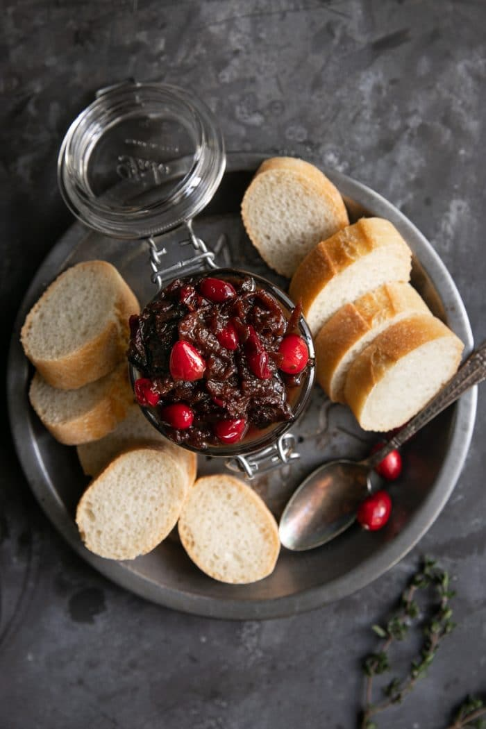 Overhead image of a tin pie dish holding a jar filled with cranberry bacon jam and sliced baguette