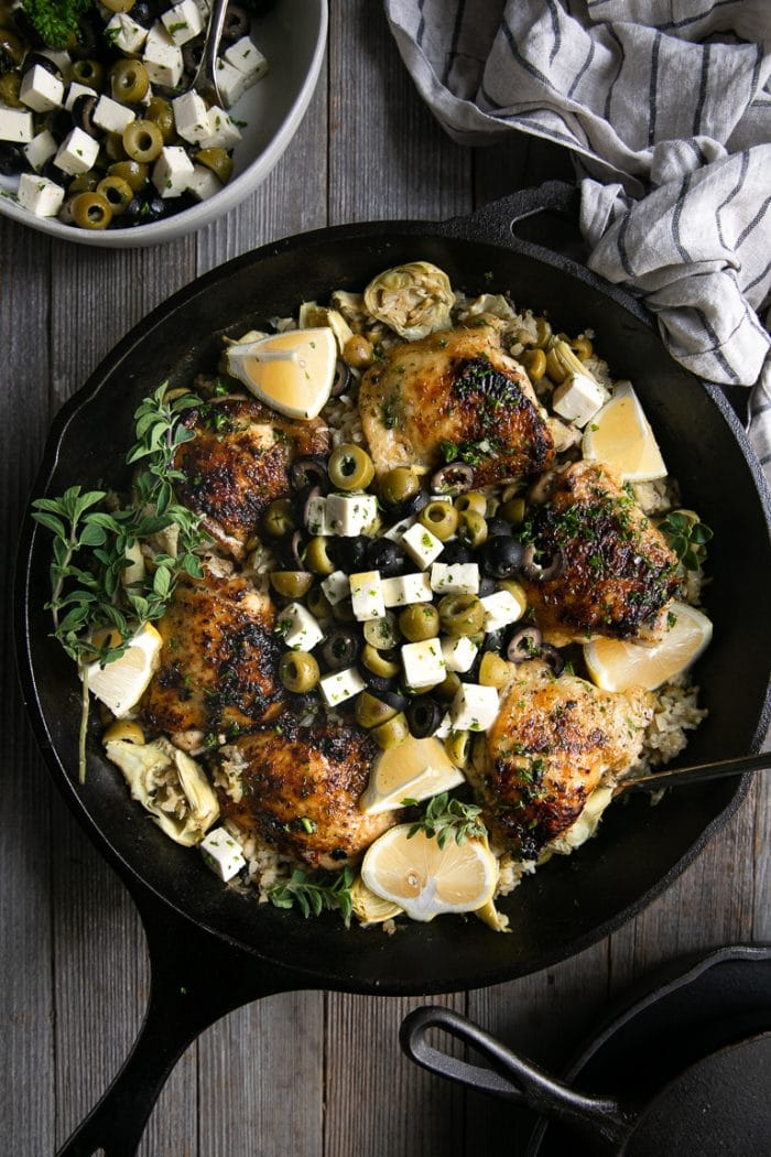 Large cast iron skillet filled with cooked bone-in skin-on chicken thighs set atop lemon rice and garnished with sliced olives and feta cheese.