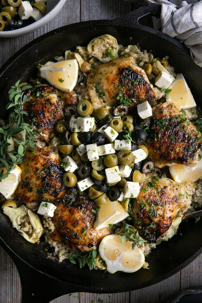 Black cast iron skillet filled with cooked chicken thighs set on top of baked lemon rice filled with green and black olives and artichokes.
