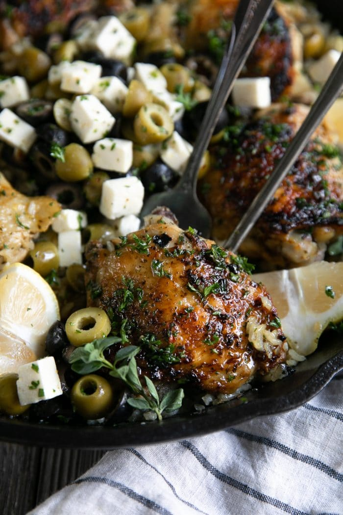 Bone-in skin-on chicken thigh cooked with rice and olives in a large cast iron pan in the oven.