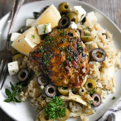 White plate filled with cooked lemon rice filled with artichoke hearts and olives and topped with a bone-in skin-on chicken thigh.