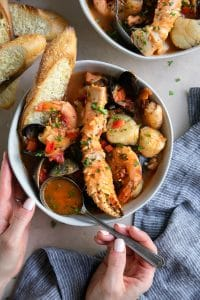 A bowl Cioppino seafood stew filled with shrimp, scallops, crab legs, fish, clams, and mussels and served with slices of bread.