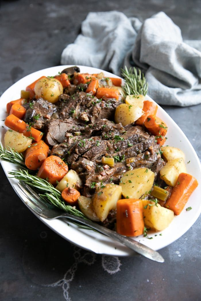 Coca-Cola Pot Roast on a white serving tray surrounded with carrots and potatoes.