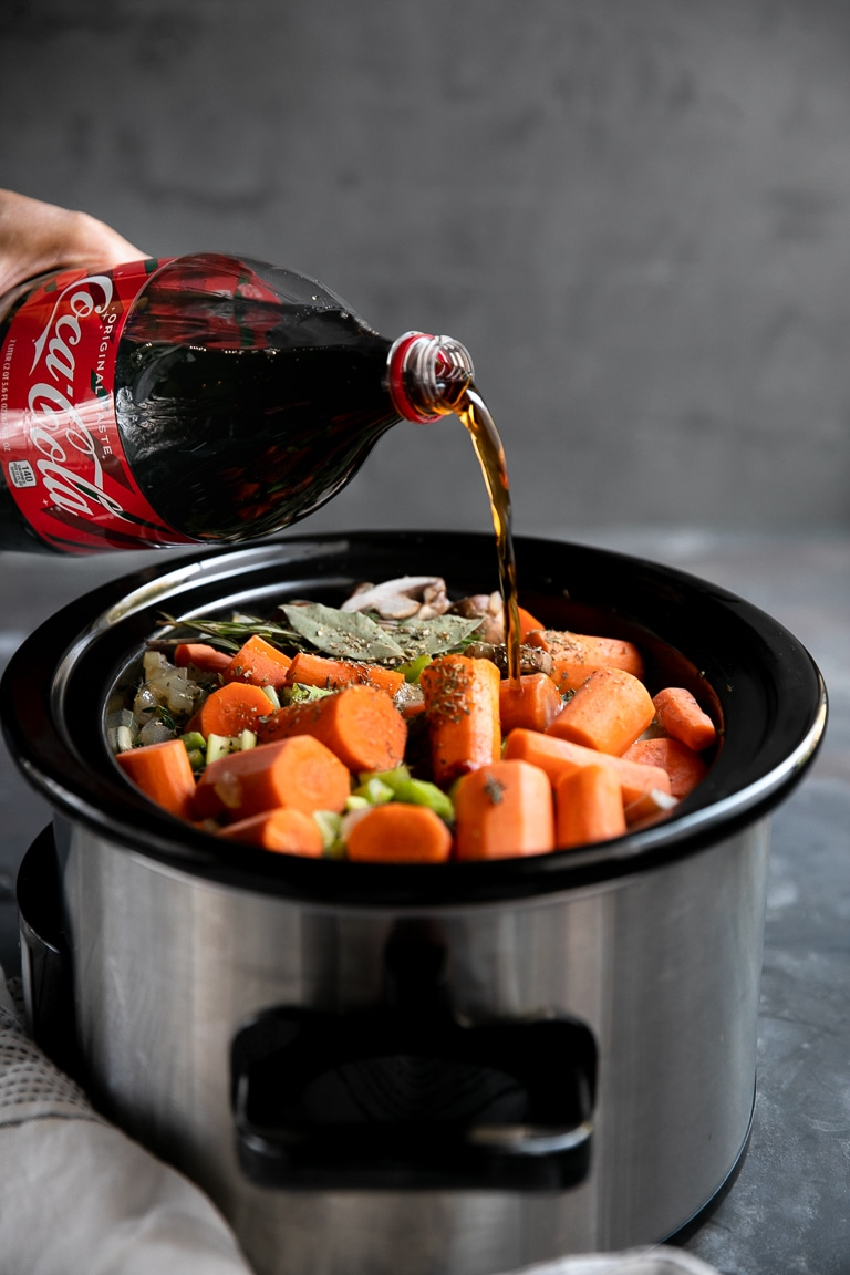 coke being poured into slow cooker pot roast