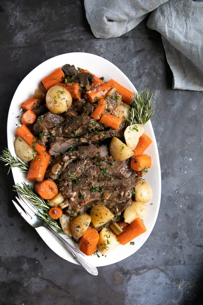 Sliced and prepared pot roast on a white plate with carrots and potatoes.