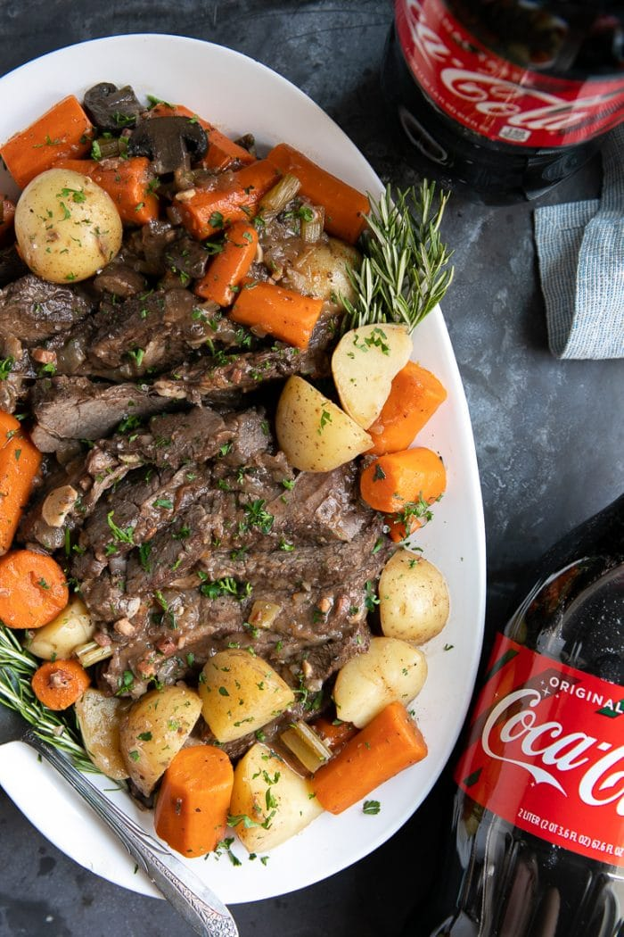 Large white serving plate with Coca Cola Pot Roast, carrots, and potatoes.